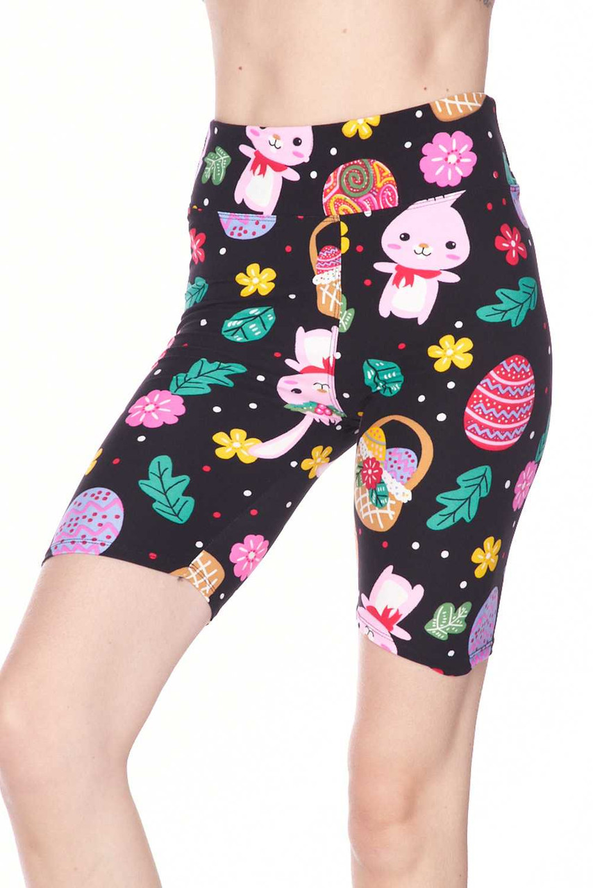 Our adorable Buttery Soft Buttery Soft Cute Bunnies and Easter Egg Shorts feature a black background contrasted by a cute spring inspired colorful cartoon design of pink bunnies, painted eggs, and pink and yellow flowers.