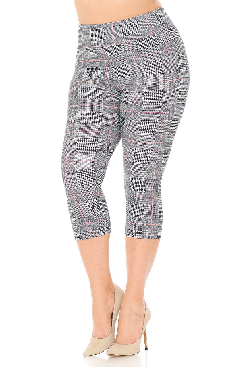 Angled front view of Buttery Soft Coral Accent Textured Houndstooth High Waist Plus Size Capris - 3 Inch with a black and white print and a peachy orange grid overlay.
