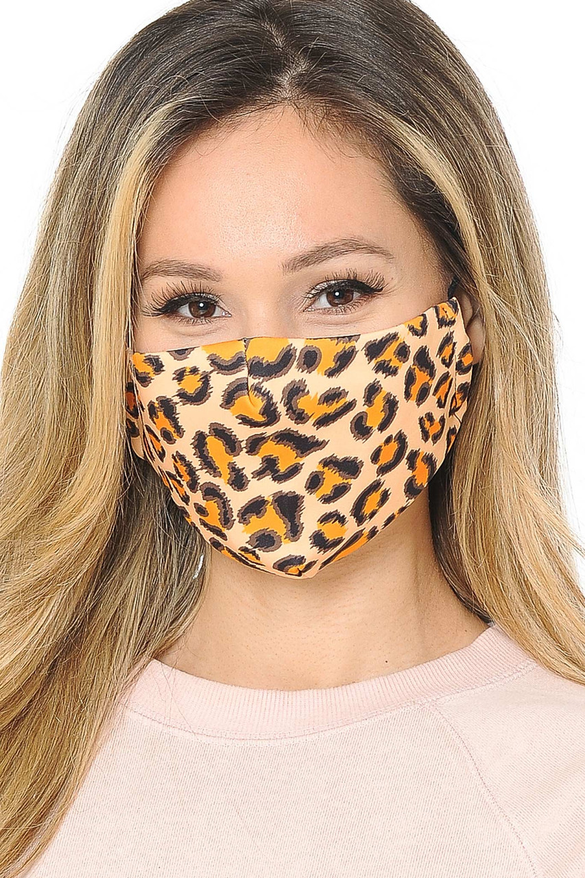 Front facing view of our fabric Creamsicle Leopard Graphic Print Face Mask with adjustable ear string sizing.