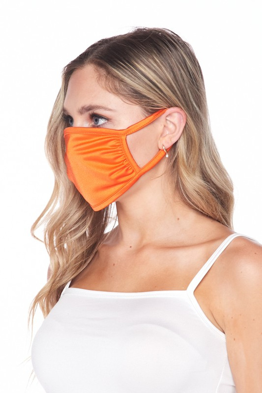 Side view of USA made orange Solid Tricot Smooth Textured Face Mask that with earloop fit.