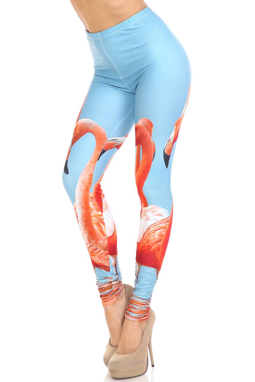 45 degree view of Creamy Soft Flamingo Leggings - USA Fashion™ with a colorful flamingo design on a sky blue background.