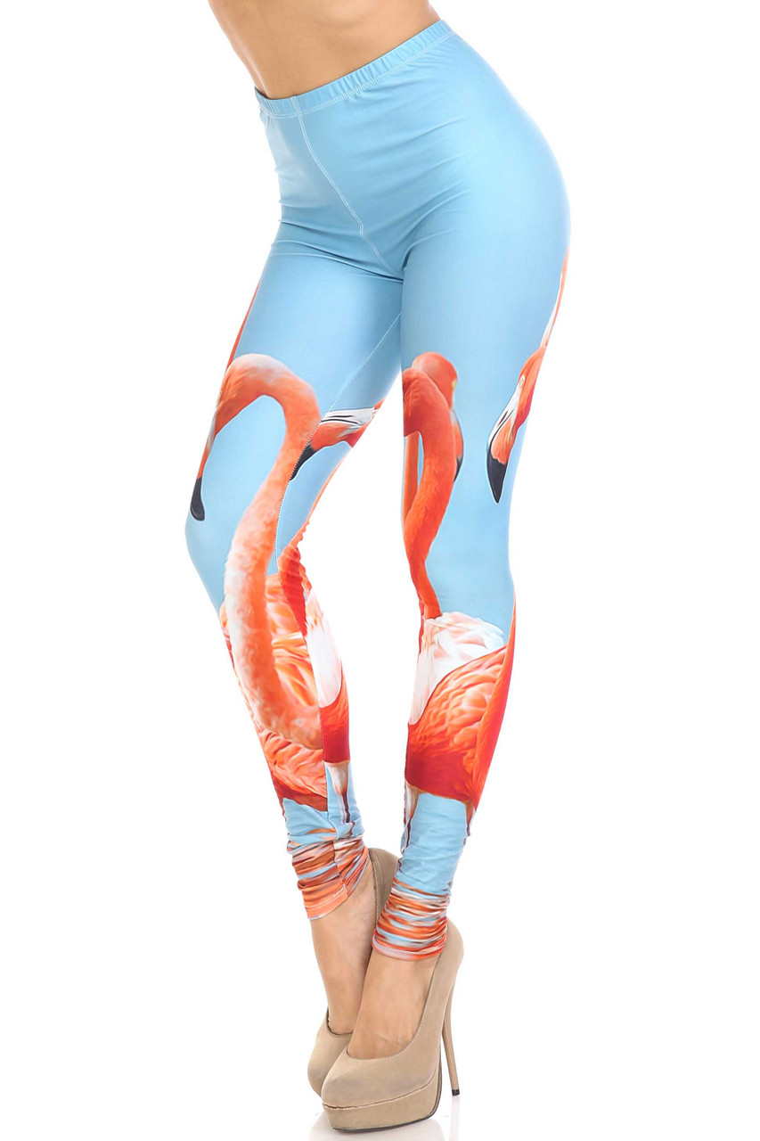 45 degree view of Creamy Soft Flamingo Plus Size Leggings - USA Fashion™ with a colorful flamingo design on a sky blue background.