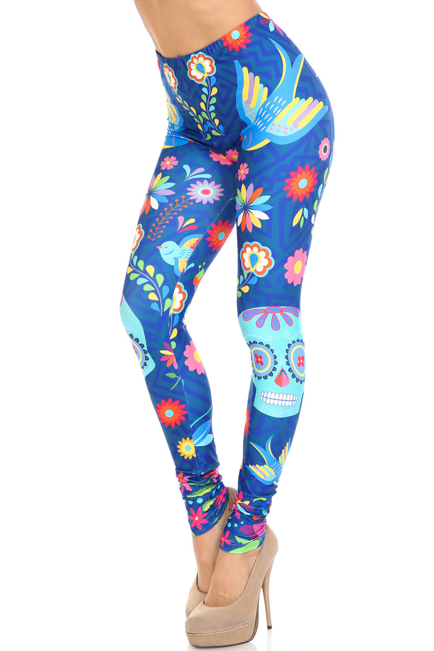 45 degree view of Creamy Soft Garden of Eden Sugar Skull Plus Size Leggings - USA Fashion™ featuring a vibrant print with sugar skulls, flowers, and birds on a blue background.