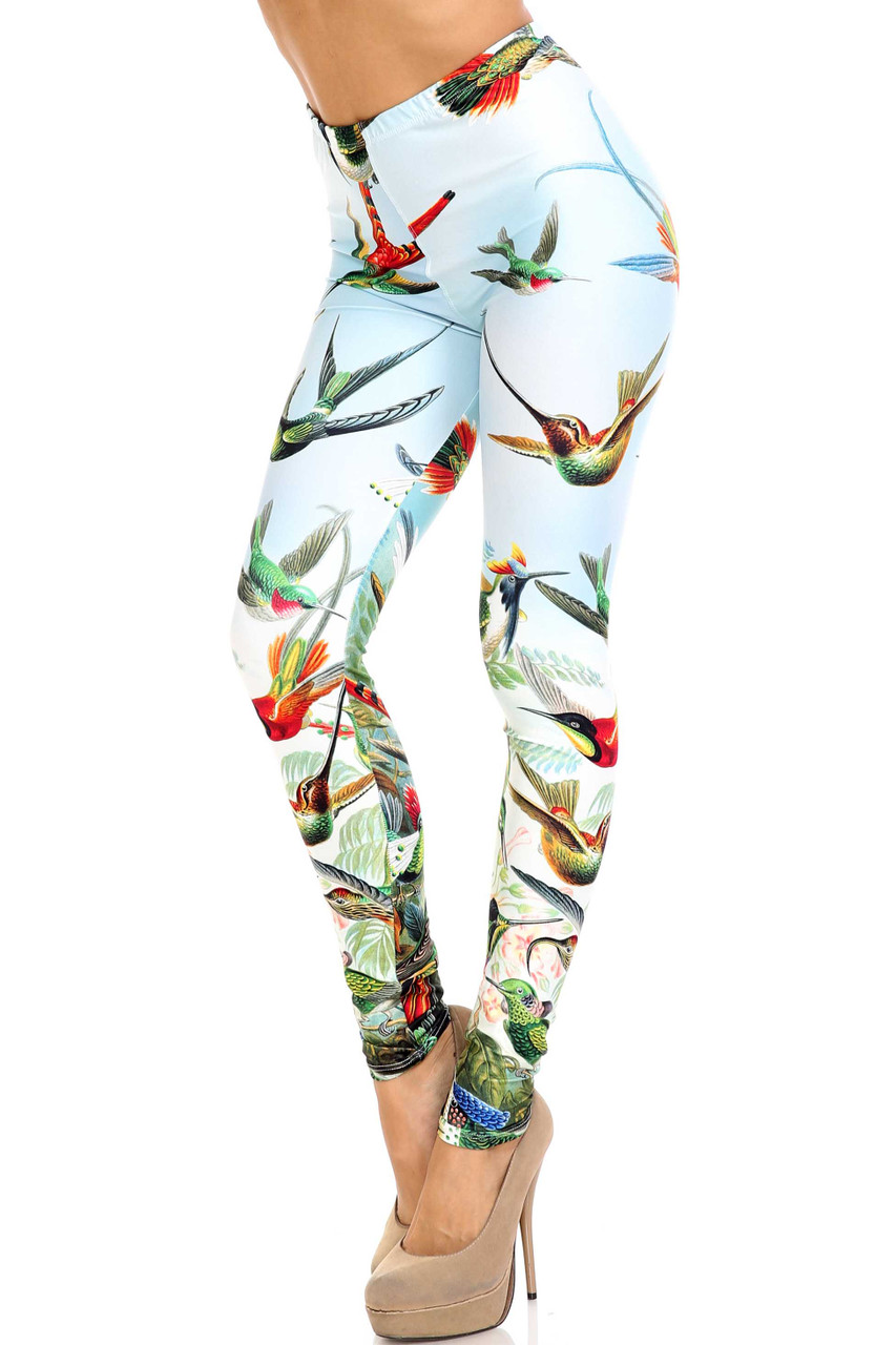 45 degree view of Creamy Soft Happy Hummingbirds Leggings - USA Fashion™ with an amazing colorful bird design contrasting a light blue background.