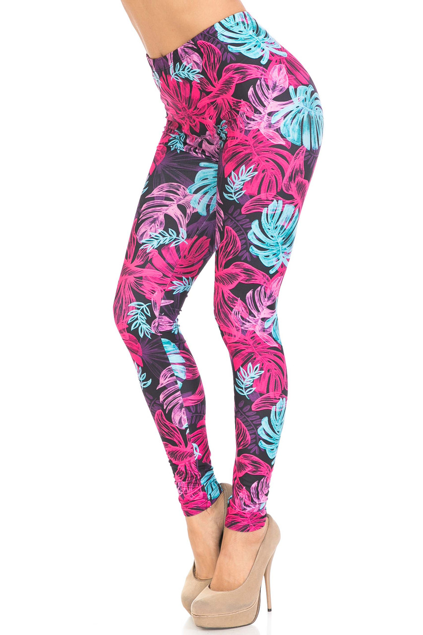 45 degree view of our Creamy Soft Vivid Tropical Leaves Plus Size Leggings - USA Fashion™ with a bright fuchsia, purple, and soft blue leaf design that contrasts a black fabric base.