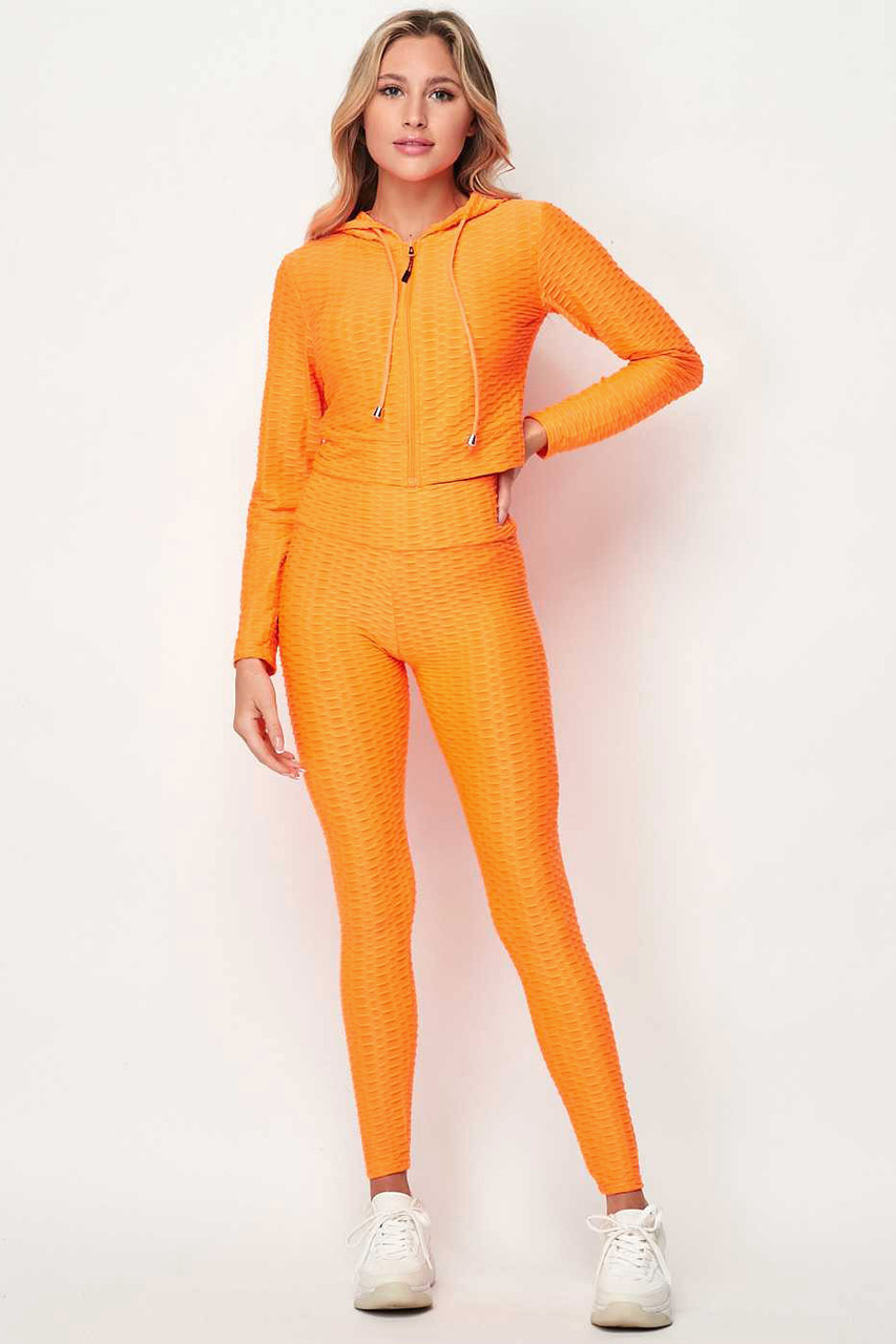 Front of Neon Orange 2 Piece Scrunch Butt Leggings and Cropped Hooded Jacket Set
