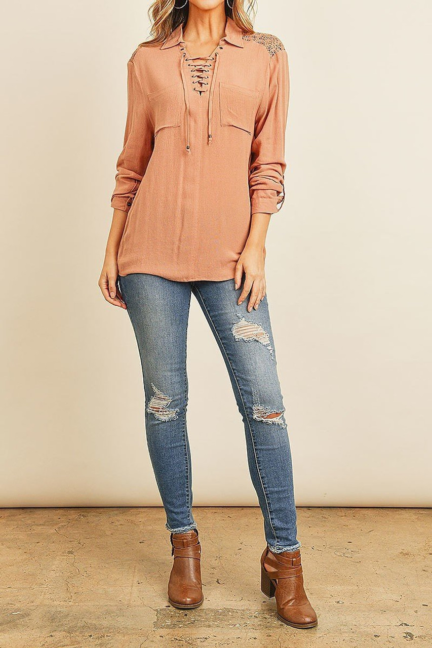 Full modeled view of Crochet Back Accent Lace Up V Neck Collared Long Sleeve Top with Front Pockets shown with distressed skinny jeans and brown leather booties.