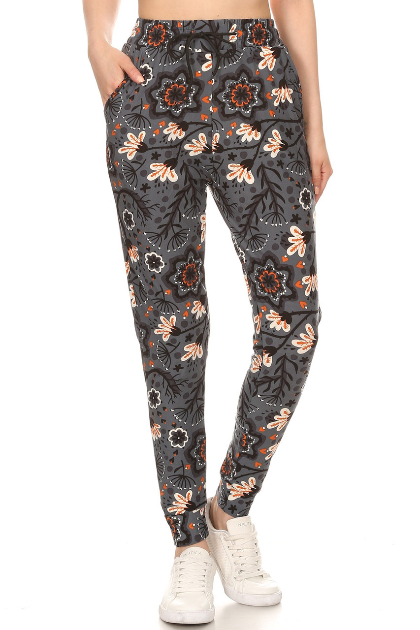 Front side of Buttery Soft Peachy Floral Blossom Plus Size Joggers with a gorgeous delicate flower design and the perfect charcoal background for any season.