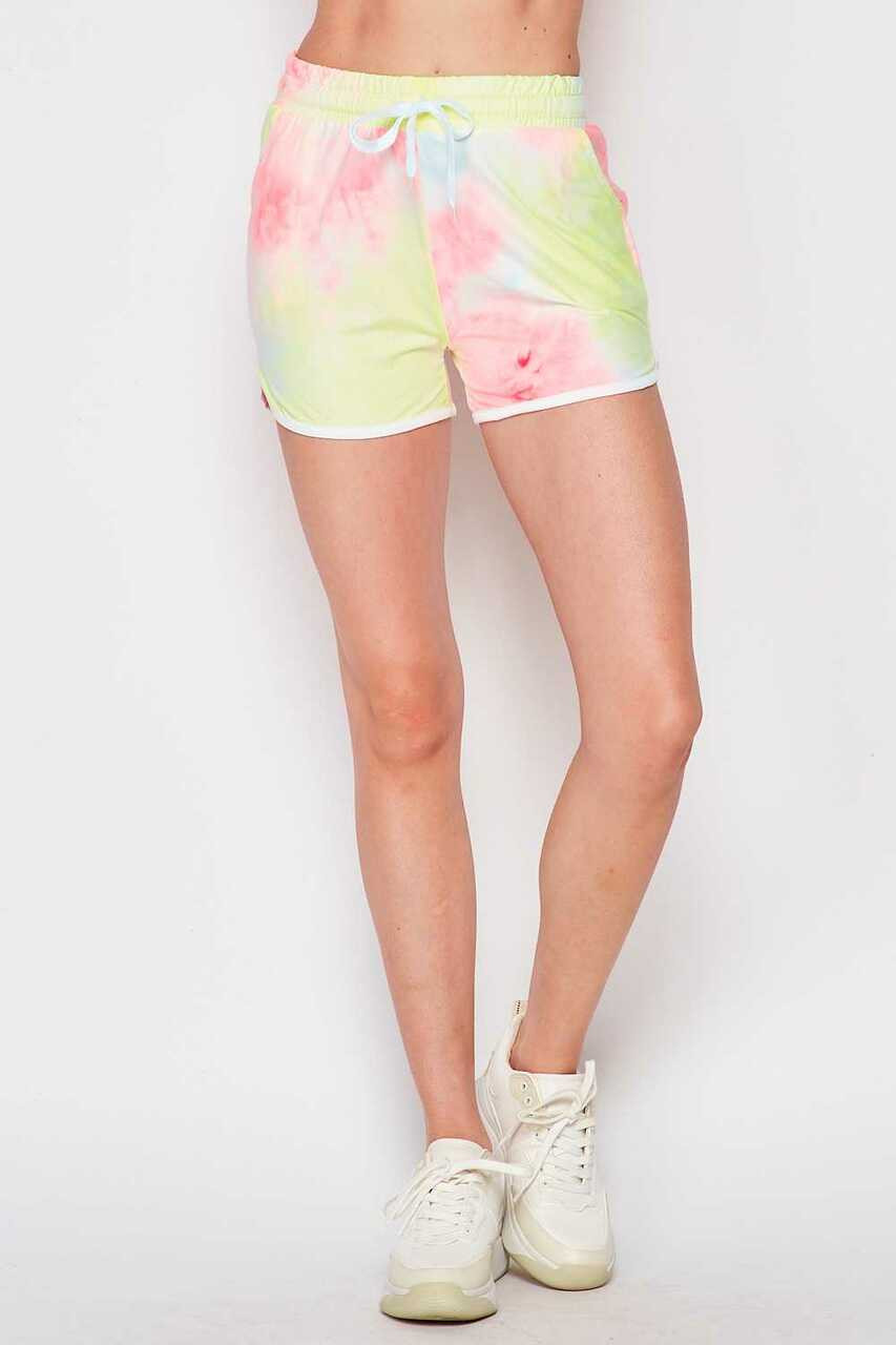 Front of Buttery Soft Pink and Yellow Tie Dye Drawstring Waist Dolphin Shorts with Pockets teamed with white sneakers