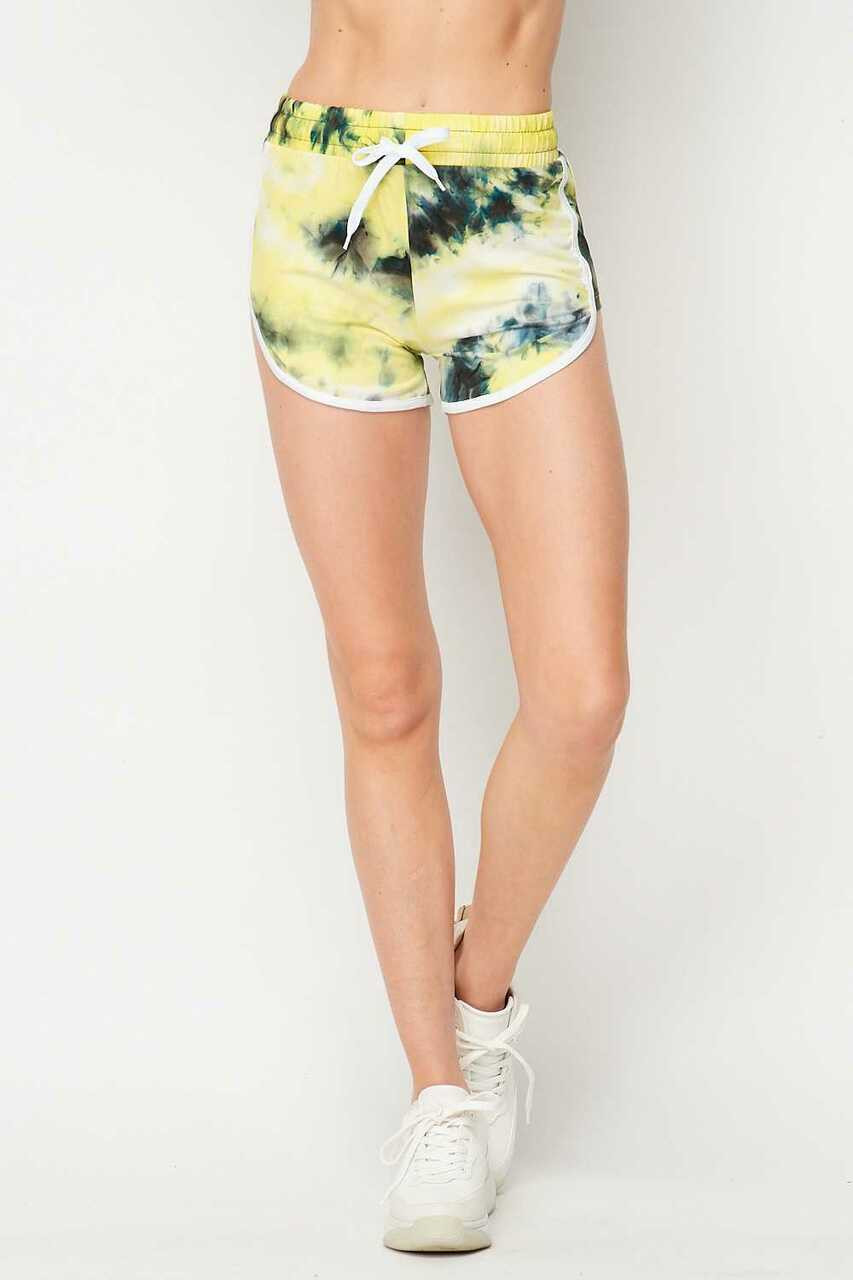 Front side of Buttery Soft Yellow Tie Dye Side Striped Drawstring Waist Dolphin Shorts shown paired with white sneakers