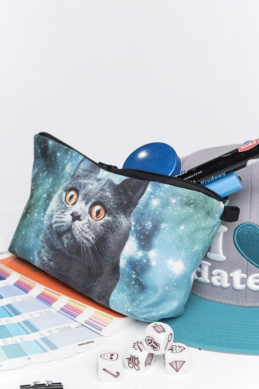 Galaxy Kitty Cat Graphic Print Makeup Bag pictured on top of a pantone book