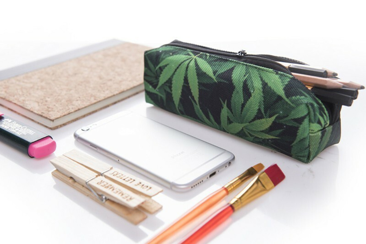 Green Marijuana Rectangular Graphic Print Pencil Cosmetics Case - 26 Assorted Styles pictured with art supplies and a phone