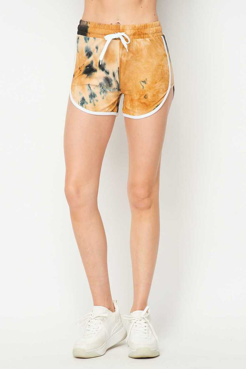 Front side image of Buttery Soft Camel Tie Dye Side Striped Drawstring Waist Dolphin Shorts shown paired with white sneakers.