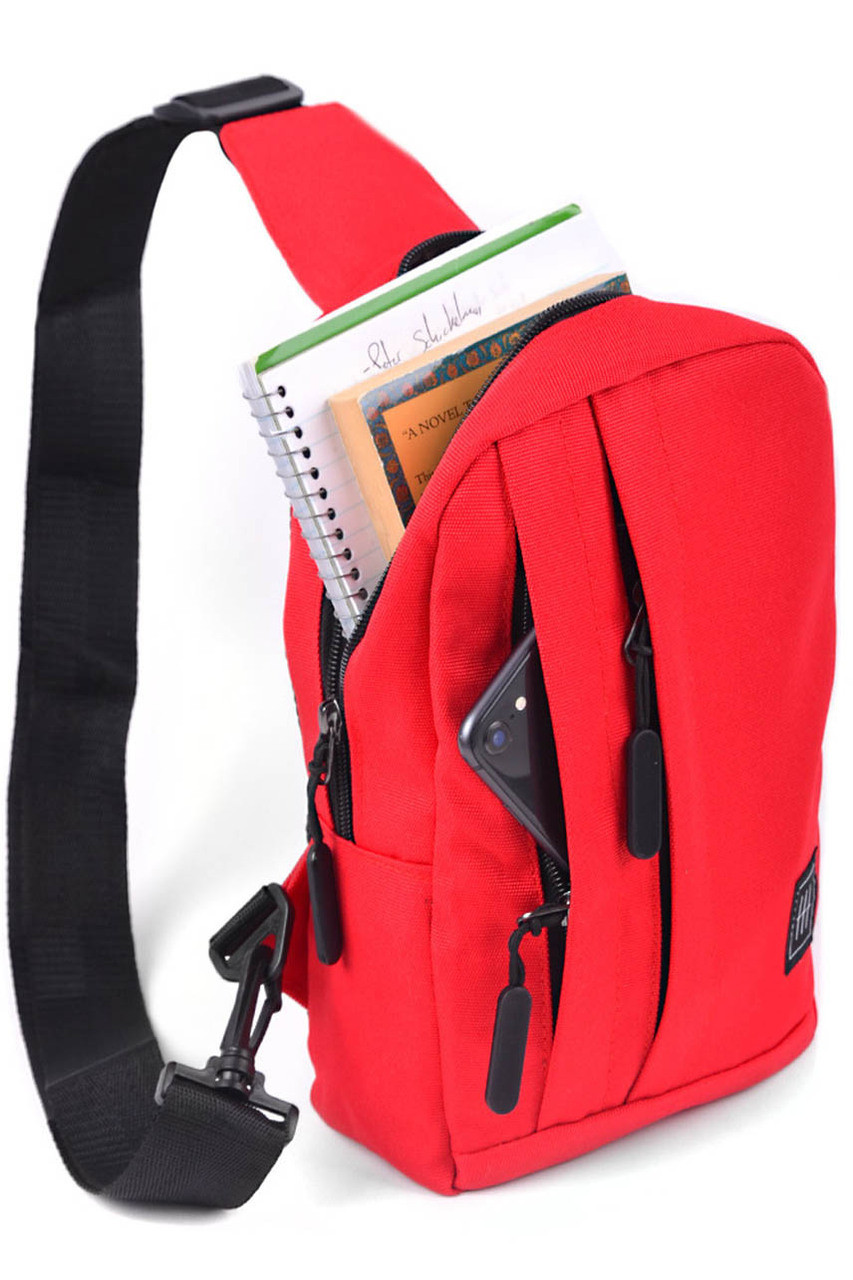 45 degree view of Red Cotton Crossbody Sling Bag with Reversible Strap - 3 Colors shown with main compartment open with books and notebook inside.
