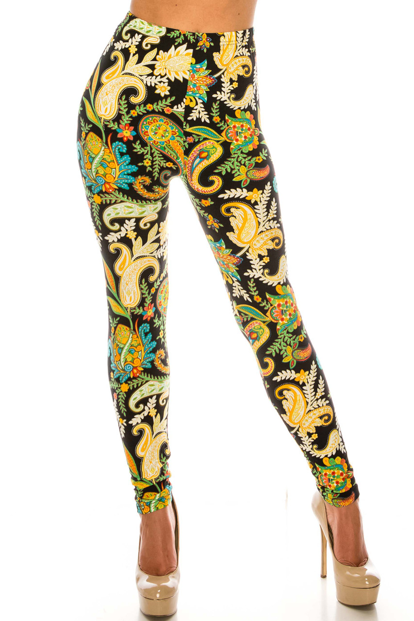 Front side image of Buttery Soft Lustered Leaf Leggings with a bright green and yellow design that boldly contrasts a black background.