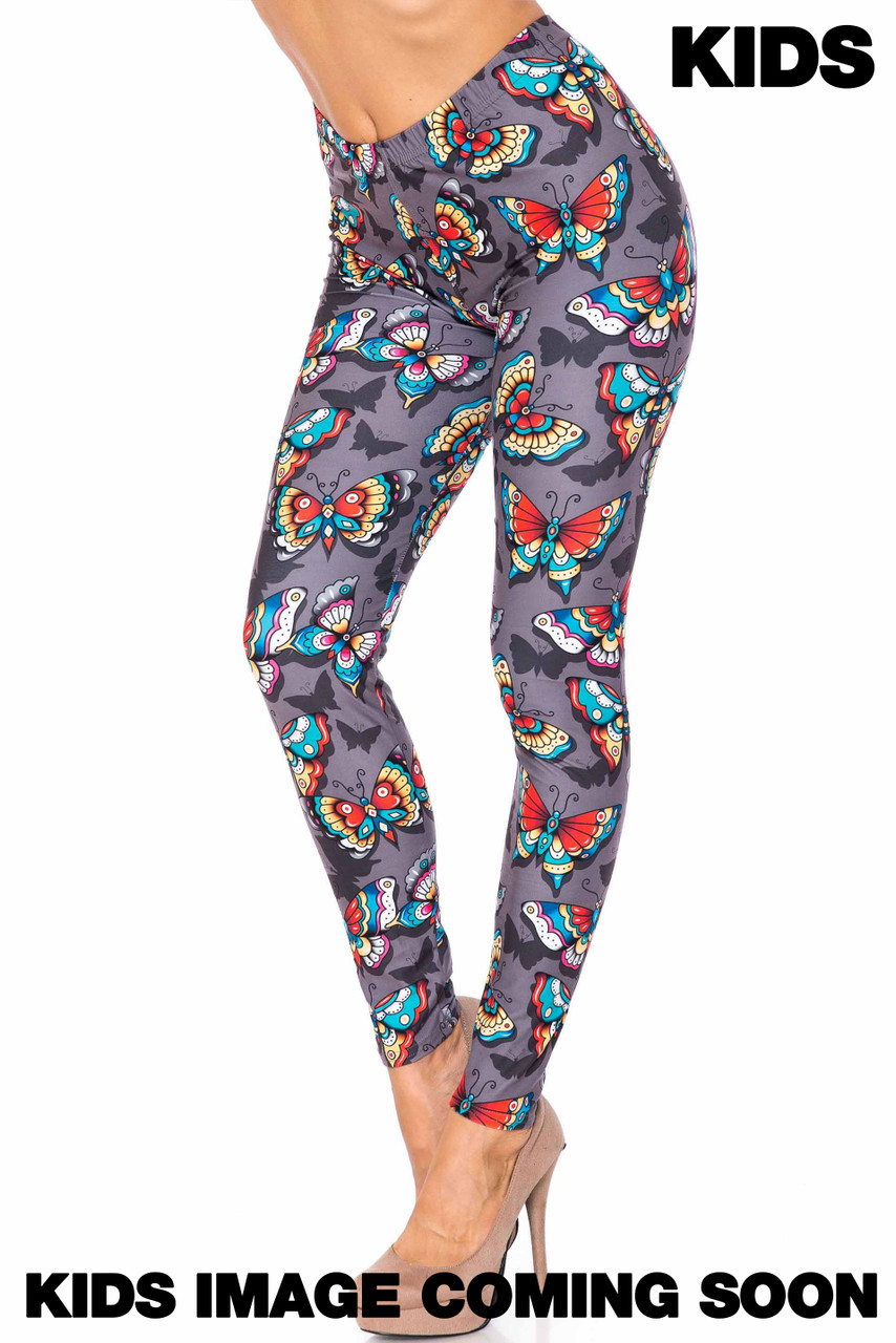 45 degree view of Creamy Soft Jewel Tone Butterfly Kids Leggings - USA Fashion™ with a colorful butterfly design on a charcoal background.