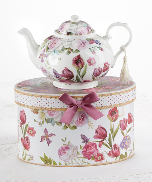 """Tulip Teapot in gift box, will brighten anyone's day with this beautiful teapot gift in its own matching print gift box with matching satin ribbon. A decorative tassel on the handle adds a lovely finishing touch. Gifting Idea: birthday gift, bridal shower, get well, treat yourself or someone you love.  Includes:  9.5 x 5.6"""" porcelain teapot Soft white background with a purple tulip floral print Dishwasher safe  Other Items Available:  Tea choices available to add to your order in the loose-leaf shop  Teas and Teaware are shipped together, Cornucopia Teas come in resealable pouches with decorative tea labels, and includes a brewing guide. If purchasing as a gift your personal message is included on the pamphlet."""
