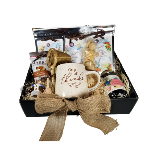 """Cup of Thanks Tea Gift Box: A thank you gift for any occasion, filled with a selection of Cornucopia's Loose-leaf teas and tea assorted treats. Give to a babysitter, professional, caregiver, to show your appreciation. They will enjoy every bite of gourmet goodness.   Includes: 1-12 oz Mug ivory speckled with a short tapered shape and message """"Oh So Thankful"""" 1-1 oz Mandarin Chai, 1-1 oz Green Tea Garden, 1-1 oz Coconut Chai, 1-1 oz Dickinsons Mini Honey 1-Wood Honey Spool 1-Bamboo Tea Strainer 1-13.4 oz Pretty Little Jam - Blueberry 1-Marich Gingerbread Bites   This gift comes in a black gift box, natural fiber fill, shrink wrapped and a handmade bow"""