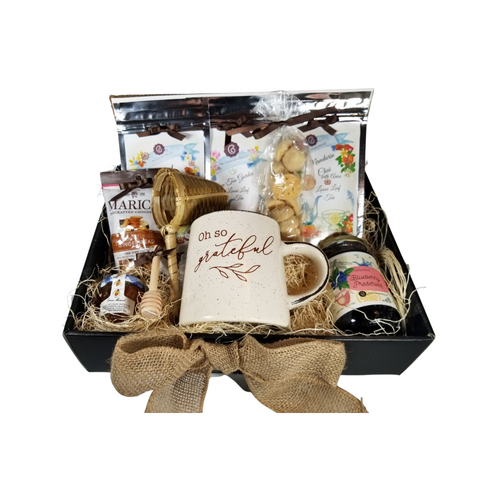 """Oh, So Grateful, Thank You Tea Gift Box: A thank you gift for any occasion, filled with a selection of Cornucopia's Loose-leaf teas and tea assorted treats. Give to a babysitter, professional, caregiver, to show your appreciation. They will enjoy every bite of gourmet goodness.  Includes:  1-12 oz Mug ivory speckled with a short, tapered shape and message """"Oh So Grateful"""" 1-1 oz Mandarin Chai, 1-1 oz Green Tea Garden, 1-1 oz Coconut Chai, 1-1 oz Dickinsons Mini Honey 1-Bamboo Tea Strainer 1-11 oz Blueberry Jam 1-Marich Gingerbread Bites 1-Tea Sugar Cookies  This gift comes in a black gift box, natural fiber fill, shrink wrapped and a handmade bow, complimentary enclosure card with your personal message."""