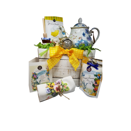 """Sunshine Garden Teapot with Tea Gift Basket: This lovely Tea and Teapot gift set with mini honey, honey spool, and teapot teaball sends happy greetings just in time for tea!  16 oz. by Homestyle Teapot. White with shades of blue and pale pink garden flowers. Dishwasher and microwave safe. 1 oz of Cornucopia Shop's Organic Loose Leaf 8T21068 Pineapple Banana Far from simply banana: this blend delightfully combines wonderful sweet aromas of exotic ripe fruits. Creamy notes support the idea of a banana-pineapple dessert. Banana slices and chips combined with small marshmallows crown this special black tea blend.Ingredients: Black tea (80 %), freeze-dried banana pieces, banana chips (banana, coconut oil), flavoring, marshmallows (glucose-fructose syrup, sugar, water, gelatine, corn starch, natural flavouring) Mini Honey by Bonne Maman 1 oz Honey Spool, Wooden, Teaball by Cha Cult, with teapot charm chain, stainless steel 2"""" ball 2.5 oz. - J&M Tea Cookies - Lemon 100% cotton, large white flour sack tea towel with Pansies in a tea cup print  Gift comes in a gift basket box shrink wrapped with hand made bow. Enclosure card with 10% off coupon on purchase of tea, and your personal gift message."""