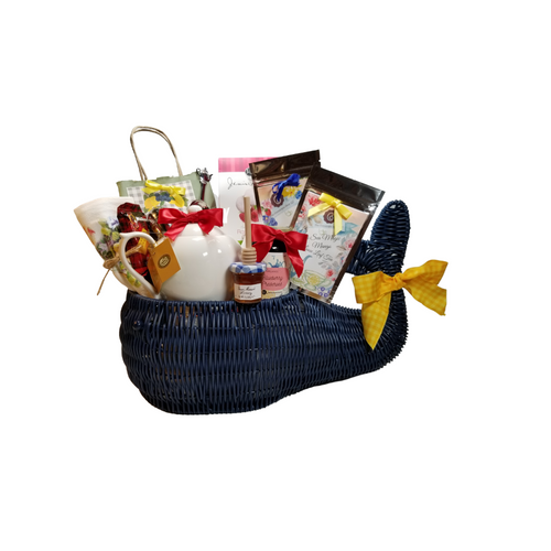 """Whale of a Good Time Gourmet - Gift Basket:  Celebrate the reopening of summer homes and cottage life with this gourmet filled Whale gift basket. The Whale gift basket is made of woven resin in nautical navy blue and his eyes are made of navy-blue beads.  The perfect center piece to great guest or thank a host. Place it on the counter, cottage kitchen table or sun porch coffee table and fill it all summer with your beach combing treasures once the goodies are gone.   Includes:  •Navy Blue Resin Whale Shaped Basket with Navy Blue Eyes   17"""" L x 8"""" W x 10 ½"""" H by tail height.  •White Classic Teapot porcelain 11.8 fl. oz  oCha Cult drop-in stainless steel tea strainer  oDishwasher safe •Teaball infuser 1 1/2 """" with drip catcher sku 41535 stainless steel by Chai Cult made in Germany  •1 oz. Cornucopia's Gourmet Raspberry & Blueberry Loose Leaf Tea 8T21202 •1 oz Cornucopia's Gourmet South Sea Magic Loose Leaf Tea 8T22302 •Mini Honey 1 oz, •Wood Honey Spool, •Tea Measuring Spoon with a Teapot handle •1.4 oz Walker Shortbread Cookies, •2.5 oz J & M Gourmet Lemon Tea Cookies •1- Lemon Scone Mix in decorative gift bag with message that says, """" You are Simply the Zest! """" •1- 100% Cotton Flour Sack Tea Towel with Pansies in a Teacup print •11- oz Cornucopia's Gourmet Blueberry Jam  Gift is wrapped in cellophane and tied with handmade bow.  Enclosure card with 10% off coupon on purchase of tea, and your personal gift message."""