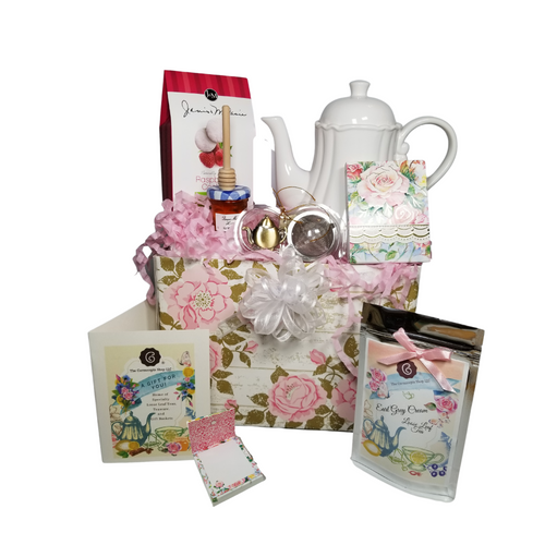 """Shabby Chic Tea Gift Set - Gift Basket Box:  Enjoy an afternoon tea and snacks with this classic white teapot by White Cliffs. This basket contains all they need for a pleasant way to create a moment of indulgence.  Sip on Cornucopia's specialty loose leaf tea and cuddle up with a good book to carry them away. What we love most is this teapot is meant for everyday use and mixes in well with any decor.  Comes in its own matching print gift box with matching satin ribbon. Great Gift Idea: New Mommy, Birthday, get well, thank you.   Gift Set Includes: •40 fl. oz Classic White Porcelain Teapot, by White Cliffs, handwash recommended.  •1 oz of Loose-Leaf Cornucopia Tea. 7T6529 Earl Gray Cream. (Loose Leaf) combines our full-bodied organic black tea with creamy vanilla essence.  oCornucopia Teas come in resealable pouches with decorative tea labels as shown in the image, along with a recipe and brewing guide.  •1 oz Mini Honey, •Wood Honey Spool, •Embossed Purse Pad, by Carol Wilson Paper Arts, pad is 3 inches x 4 inches and has 100 coordinating patterned pages and a magnetic closure, •1 1/2 """" Teaball with Teapot charm chain, stainless steel by Chai Cult (Germany) •J & M Gourmet Raspberry Tea Cookies •Teas and Teaware are shipped together. •Gift comes in cottage rose gift basket box, shrink wrapped in cellophane and hand tied gift bow. Enclosure card with your personal gift message 200-character limit.  Note: Teapot handle style may vary slightly from picture shown."""