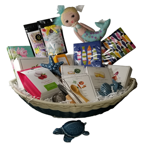"""Welcome to the Summer Home - Gift Basket: A wonderful gift for a new cottage owner or reopening the summer season. Designed for a lake house or summer cottage. This sturdy resin wicker boat comes pre-stocked with goodies and keepsakes, a journal to log guest comments, and summer fun, guest paper towels, and matching luncheon napkins in nautical blue fish print, seaside candle holders, & nick knacks, and mermaid hanger, and an array of gourmet treats from the Cornucopia Epicure Shop.  When we chose this boat basket, we envisioned by summers end it could be filled with beach combers shells, driftwood, and sea glass, or pinecones, and beach rocks and become a treasured centerpiece. Many possibilities to add to the charm of a summer home. *Gourmet Food products are made in the USA by Jocelyn & Co. and are shelf stable.  Gifting ideas: New Summer Home, Hostes gift, Guest House Gift  Includes:  Boat shaped resin wicker basket, Hanging Mermaid Doll, Summer Journal by Carol Wilson Art Papers & Stationary Ceramic Sea Creatures, starfish, and turtle Ceramic Candle Holders, starfish, and seashell, Mini wood Condiment Spoon, Mini Cheese Spreader, *Mini Whisk, & three 1 oz Gourmet Dip Mixes, Garlic & Cheese, Rustic Vegetable, Parmesan & Artichoke Tea Ball Infuser 1"""" stainless steel by Cha Cult 2 -1 oz Loose Leaf Teas, by The Cornucopia Tea Shop South Sea Magic Mango, black tea, flavoring, rose petals, sunflower blossoms, cornflower blossoms Decaffeinated Ceylon Ice is a rich, Sri Lankan black iced tea that is 98% caffeine-free. Each package contains a total of 8 one-quart brew bags *2 oz Gourmet Amber Beer Mustard, *5 oz Hardwood Smoked Summer Sausage, *8 oz Cheddar Cheese Bar 7"""" tall x ¾ """"thick, *3.75 oz Cabernet Sauvignon Cheddar Cheese Spread, a creamy spreadable cheese made with real cabernet sauvignon wine, and cheddar cheese. Size: 4Hx4Wx1D 75 oz Camembert Cheese Spread, a white cheddar and camembert cheese spread creamy and so amazing! Size: 4Hx4Wx1D *4 oz Olive Oil & Sea"""