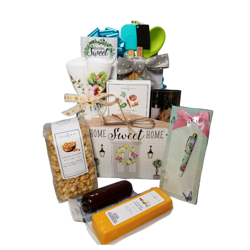 """Linen n Things New Home Gift Box: From Cornucopia's Epicure Shop, this new home showcase of gourmet specialties and gifts is ideal for the lady of the house. Filled with linens, kitchen tools and an array of shelf-stable, cheeses, Summer Sausage, Gourmet Crackers, Dip mixes, and Vanilla Caramel Popcorn, (by Jocelyn & Co) hard candy in a Home Sweet Home box.  Includes:  Reusable Gift Box Wood and Silicone Spoon & Spatula Set Stainless Steel Cleaver Apron, Adult size light blue apron with floral pattern, gray and white polka dots that has hidden pocket. Made of 100% cotton. 33"""" H x 28"""" W. Tea Towel Set, soft 100% cotton large white flour sack tea towel featuring 2 classic Carol Wilson designs. Refrigerator magnet pad Shopping List w/pen by Carol Wilson Artful paper designs. Home Sweet Home Candy box of strawberry hard candy *Mini Whisk, & 3 - 1 oz Gourmet Dip Mixes, Garlic & Cheese, Rustic Vegetable, Parmesan & Artichoke *5 oz Hardwood Smoked Summer Sausage, *8 oz Cheddar Cheese bar 7"""" tall x ¾ """"thick, 4 oz bagged Vanilla Caramel Popcorn 9"""" tall x 2.5"""" D, Crispy olive oil and sea salt crackers Size: 3.75Hx2.75Wx 1.0D / 0.9 oz. (25.515G).  *Gourmet Food products are made in the USA and are shelf stable.  Gift comes wrapped in cellophane, matching ribbon, and paper shred fill. A complimentary gift card with your personal message."""