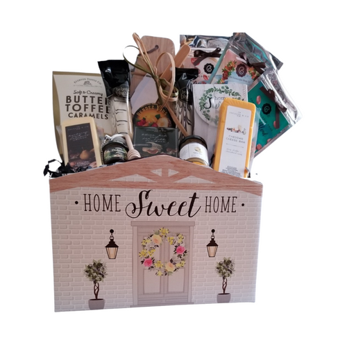 """From Our Home to Yours - Gift Box: From Cornucopia's Epicure Shop, a showcase of gourmet specialties and gifts. Starting with the Paddle Cutting Board and Cleaver, to the assortment of shelf-stable, Cheeses, Summer Sausage, Gourmet Crackers, (by Jocelyn & Co), and Rendezvous Tin of assorted fruit flavored hard candy. and much more! Simply delicious gift.   Gifting Ideas: for a new home for friends, family, coworker, or employee. Great Realtors appreciation gift.  Includes:  Reusable Gift Box Paddle Cutting Board Stainless Steel Cleaver, An assortment of Cornucopia's Gourmet Coffee and Loose-Leaf Tea, 1 oz each Decaffeinated Gourmet Coffee Beans Gourmet Coffee Beans Café Latte Black Tea (Loose Leaf): this exquisite and unique mixture also holds a unique flavor of coffee and chocolate and cream in your tea, coffee ooh la la, the perfect morning tea! Mini honey, Honey Spool, Stainless Steel Tea Infuser 1 ½ ball with chain by Chai Cult Butter Toffee Caramel Candies Boxed Strawberry Hard Candies in Home Sweet Home theme box, 2 Hazelnut Biscotti Cookies, *2 oz Gourmet Amber Beer Mustard, *5 oz Hardwood Smoked Summer Sausage, *8 oz Jalapeno Monterey Jack Cheese bar 7"""" tall x ¾ """"thick, *8 oz Cheddar Cheese bar 7"""" tall x ¾ """"thick, 5 oz Rendezvous Tin of assorted fruit hard candy drops .9 oz Olive Oil & Sea Salt Cracker  *Gourmet Food products are made in the USA and are shelf stable.  Gift comes wrapped in cellophane, matching ribbon, and paper shred fill. A complimentary gift card with your personal message."""