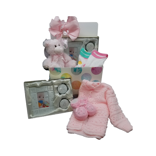 New Baby Keepsake - Gift Basket Box: Traditional crocheted keepsake newborn baby sweater set in pink or blue with matching booties, ribbon trimmed, Baby's First keepsake set that includes a photo frame, first curl and tooth box, engravable lids. 2 bodysuits, plush bear and a reusable storage box for the nursery. A sweet gift to send your congratulations.  Comes in choice of Pink or Blue and Includes:  Baby nursery storage box, Newborn baby sweater crocheted, is practical yet a lovely keepsake of when baby was born. Sweater buttons down front for easy dressing. Made of 100% acrylic, it's machine washable. Newborn booties crocheted, make a great new baby gift or baby shower gift! Sold in assorted styles of pink, and pink and white. 2 cotton bodysuits Baby's First keepsake gift set includes a picture frame which holds a 2 inch by 3-inch photo, and 2 small keepsake boxes. One box is for baby's first curl and the other box is for the first tooth. The lids for the 2 boxes can each be engraved. A great gender-neutral baby gift! Plush bear, extra soft in pink or blue.  Complimentary enclosure card, tucked inside with your message. This gift comes wrapped in cellophane and topped with a handmade bow of Pink or Blue and It's a boy or It's a girl curled ribbon.