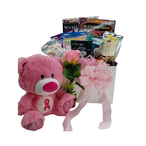"""Healing Wishes -Pink Ribbon Bear Care Basket: This healing wish care basket is filled with thoughtful items that provide, a message that it's okay to take it easy and heal. It's filled with healthy treats, a little fun, and lots of loving thoughts. A pink ribbon plush bear, so soft and cuddly. Healthy tea, (great for chemo patients) mini honey, and tea ball to help keep them hydrated, chicken soup base mix. And when they're feeling better, adult coloring books and colored pencils and a flower potted pen just to add a little silly to work on crossword and word find puzzle books, and a little sweet option with Raspberry or shortbread cookies to have with their tea.  Plush Pink Ribbon Care Bear for those who are facing breast cancer treatment, Potted Rose Pen, 2 Adult Coloring Books, Colored Pencil Set, Crossword and Word Find Puzzle Books, 1 oz 12 cups Cornucopia's Detox Tea (Loose Leaf) Ingredients: Organic lemongrass leaf, organic echinacea purpurea herb, organic licorice root, organic dandelion root, organic peppermint leaf, organic Tulsi leaf and organic ginger root. 1 1/2"""" Tea Ball, stainless steel, Dickinson's Mini Honey 1 oz, Honey Spool wooden, Chicken Noodle Soup Base, by Rabbit Creek for the Cornucopia Shop, East Shore Dipping Pretzel, 4 oz Walker's Fingers Shortbread Cookie -2 pack, 5 oz J & M Raspberry Tea Cookies.  Gift comes wrapped in cellophane with hand tied bow, a complimentary enclosure card with your personal get well message"""