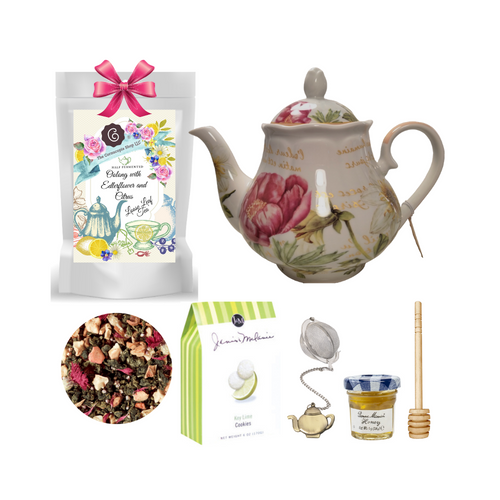 "Daylily Dreaming Teapot with Tea Gift Set: This lovely Tea and Teapot gift set with mini honey, honey spool, and teapot teaball sends happy greetings just in time for tea!   16 oz. by Kent pottery Teapot. White with Daylily floral print in shades of pink. Dishwasher and microwave safe. 1 oz of Cornucopia Shop's Organic Loose Leaf WT212062 Half-fermented (Oolong)tea blend, flavored Elderflower/Citrus. The harmony between our very aromatic, Chinese Oolong Ti Kuan Yin and the delicate characteristic notes of the elderflower is simply perfect. This composition gets a further twist from the sweet, yet tangy nuances of citrus fruits. Ingredients: half-fermented tea (58%), apple pieces, apple cubes, natural flavoring, heather blossoms, red cornflower blossoms  Mini Honey by Bonne Maman 1 oz  Honey Spool, Wooden,  Teaball by Cha Cult, with teapot charm chain, stainless steel  2"" ball   2.5 oz. - J&M Tea Cookies - Key Lime  Gift comes in a gift basket tray shrink wrapped with hand made bow.  Enclosure card with 10% off coupon on purchase of tea, and your personal gift message."