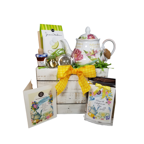 """Daylily Dreaming Teapot with Tea Gift Set: This lovely Tea and Teapot gift set with mini honey, honey spool, and teapot tea ball sends happy greetings just in time for tea!  16 oz. by Kent pottery Teapot. White with Daylily floral print in shades of pink.Dishwasher and microwave safe. 1 oz of Cornucopia Shop's Organic Loose Leaf WT212062 Half-fermented (Oolong)tea blend, flavored Elderflower/Citrus. The harmony between our very aromatic, Chinese Oolong Ti Kuan Yin and the delicate characteristic notes of the elderflower is simply perfect. This composition gets a further twist from the sweet, yet tangy nuances of citrus fruits. Ingredients: half-fermented tea (58%), apple pieces, apple cubes, natural flavoring, heather blossoms, red cornflower blossoms  Mini Honey by Bonne Maman 1 oz  Honey Spool, Wooden,  Teaball by Cha Cult, with teapot charm chain, stainless steel 2"""" ball  2.5 oz. - J&M Tea Cookies - Key Lime  Gift comes in a gift basket tray shrink wrapped with hand made bow. Enclosure card with 10% off coupon on purchase of tea, and your personal gift message."""
