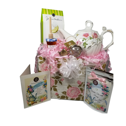"Humming Bird Teapot with Tea Gift: This lovely Tea and Teapot gift set with mini honey, honey spool, and teapot teaball sends happy greetings just in time for tea!   16 oz. by Kent pottery Teapot, White with Humming Bird and Rose floral print in shades of pink with gold trim.  Dishwasher and microwave safe. 1 oz of Cornucopia Shop's Organic Loose Leaf 7T6410 White Peony (Loose Leaf) is a delicate, crisp white tea known for its neutral, nut-like character. Ingredients: Organic white tea. Taste: Spring Fruit & Flowers (Loose Leaf) offers a light, floral flavor profile with a subtle berry finish. Mini Honey by Bonne Maman 1 oz Honey Spool, Wooden  Teaball by Cha Cult, with teapot charm chain, stainless steel  2"" ball  2.5 oz. - J&M Tea Cookies - Lime or Lemon    Gift comes in a gift basket tray shrink wrapped with hand made bow.  Enclosure card with 10% off coupon on purchase of tea, and your personal gift message."