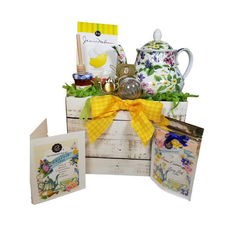 """Botanical Teapot with Tea Gift: This lovely Tea and Teapot gift set with mini honey, honey spool, and teapot tea ball sends happy greetings just in time for tea!  16 oz. by Kent pottery. white with botanical floral print in shades of green, white, pink and yellow.Dishwasher and microwave safe. 1 oz of Cornucopia Shop's Organic Loose Leaf 7T6345 Lemon Essence with Peel (Loose Leaf) combines organic green rooibos and black tea with citrus. Ingredients: Organic green rooibos, organic black tea, organic lemon peel and organic lemon myrtle. Taste: a full-bodied black tea brew with a splash of citrus zest and a subtle sweetness, provided by the green rooibos. Mini Honey by Bonne Maman 1 oz Honey Spool, Wooden Teaball by Cha Cult, with teapot charm chain, stainless steel 2"""" ball 2.5 oz. - J&M Tea Cookies - Lemon    Gift comes in a gift basket tray shrink wrapped with hand made bow. Enclosure card with 10% off coupon on purchase of tea, and your personal gift message."""