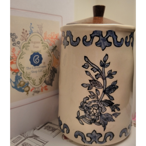 Earthenware Tea Canister: Rough hued Tea Canister gives this piece character with a wood air tight lid.  Cream background with Blue flower print. Easily incorporates into any kitchen decor.   Care: Handwash.