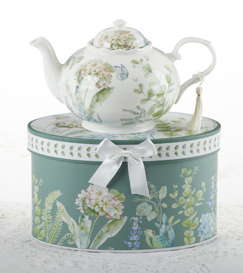 """Blue Hydrangea Teapot in gift box, will brighten anyone's day with this beautiful teapot gift in its own matching print gift box with matching satin ribbon. A decorative tassel on the handle adds a lovely finishing touch. Gifting Idea: birthday gift, bridal shower, get well, treat yourself or someone you love.  Includes:  9.5 x 5.6"""" teapot Soft white background with a Blue Hydrangea and pastel floral print Dishwasher safe  Other Items Available:  Matching cup and saucer available D8151-4  Tea choices available to add to your order in the loose-leaf shop  Teas and Teaware are shipped together, Cornucopia Teas come in resealable pouches with decorative tea labels, and includes a recipe and brewing guide. If purchasing as a gift your personal message is included on the pamphlet."""