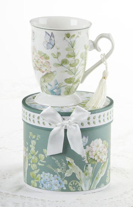 """Blue Hydrangea Mug in gift box, will brighten anyone's day in its own matching print gift box with matching satin ribbon. A decorative tassel on the handle adds a lovely finishing touch. Gifting Idea: birthday gift, bridal shower, get well, treat yourself or someone you love.  Includes:  4.9"""" Mug in gift box Soft white background with a floral print Dishwasher safe  Other Items Available:  Tea choices available to add to your order in the loose-leaf shop Teas and Teaware are shipped together, Cornucopia Teas come in resealable pouches with decorative tea labels, and includes a recipe and brewing guide. If purchasing as a gift your personal message is included on the pamphlet."""