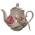 Daylily Dreaming Teapot and Tea Gift: 16 oz. by Kent pottery White with Daylily floral print in shades of pink. Dishwasher and microwave safe. Enjoy 2 oz. of Cornucopia Shop's Organic Loose Leaf Tea in this bright and cheery teapot. Tea choices available with order, ships together in decorative tea packaging.