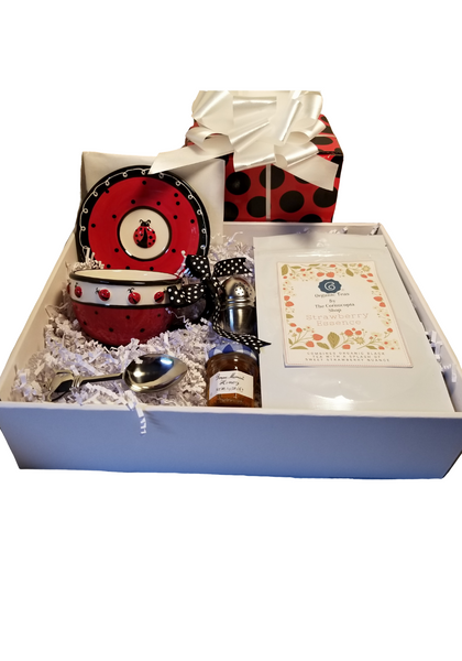 """Lady B Teacup and Saucer with Tea Gift Box, is a sweet way to send your best whishes, a happy birthday. This special gift comes with 3oz of Cornucopia's Strawberry Essence  Tea Notes:  Strawberry Essence (Loose Leaf) combines organic black tea with a splash of sweet strawberry nuance. Ingredients: Organic black tea, organic hibiscus, natural flavor and organic rose petals. Taste: A full-bodied black tea brew with a fruity finish. Origin: Sourced from family tea gardens in the Darjeeling and Assam regions of India's Banaspaty Tea Estate.  Includes:  Lady B Teacup and Saucer comes with a black polka dot bow on the handle, 1oz Mini Bonne Maman Honey, Teapot Stainless Tea Measuring Spoon, Tea Ball with rest 1.58""""  Completed gift measures 10"""" long by 10"""" wide and 3"""" tall and weighs 2 pounds.  This gift comes wrapped in cellophane and topped with a whit bow, red and black polka dot gift box."""