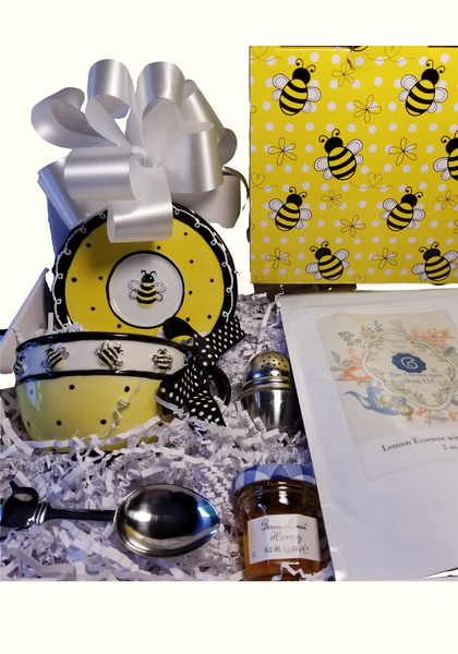 """This little Bizzie Bee Teacup and Saucer with Tea Gift Box, is a sweet way to send your best wishes, or happy birthday. This special gift comes with 3oz of Cornucopia's Lemon Essence with Lemon Peel Tea. A great gift to add or begin a Teacup collection.  Tea Notes:  Lemon Essence with Peel (Loose Leaf) combines organic green rooibos and black tea with citrus Ingredients: Organic green rooibos, organic black tea, organic lemon peel and organic lemon myrtle. Taste: a full-bodied black tea brew with a splash of citrus zest and a subtle sweetness, provided by the green rooibos. Origin: Sourced from family tea gardens in the Darjeeling and Assam regions of India.  Includes:  Bizzie Bee Teacup and Saucer comes with a black polka dot bow on the handle, 1oz Mini Bonne Maman Honey, Teapot Stainless Tea Measuring Spoon, Tea Ball with rest 1.58"""", 3oz of Lemon Essence with Lemon Peel Cornucopia Loose Leaf Tea  Completed gift measures 10"""" long by 10"""" wide and 3"""" tall and weighs 2 pounds.  This gift comes in a white gift box with white crinkle paper fill,wrapped in cellophane shrink wrap and topped with a white bow, Bumble Bee print gift box."""