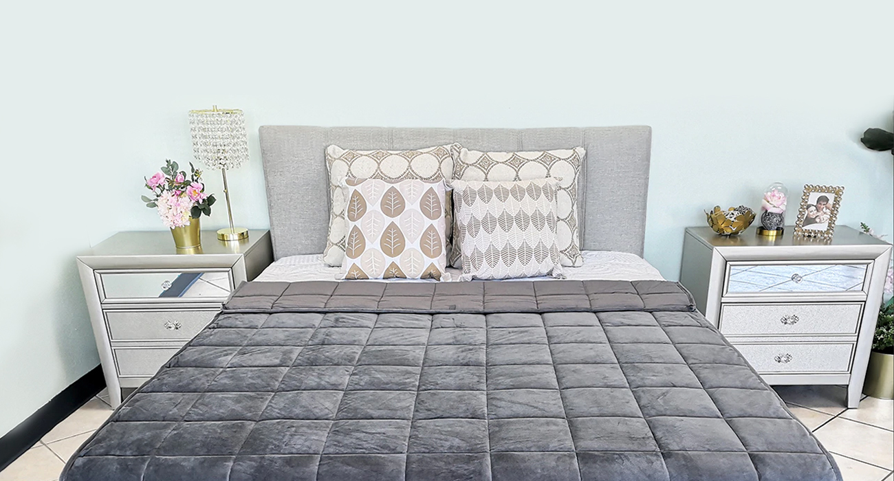 Sweet Zzz Weighted Blanket folded on a mattress in a luxury bedroom