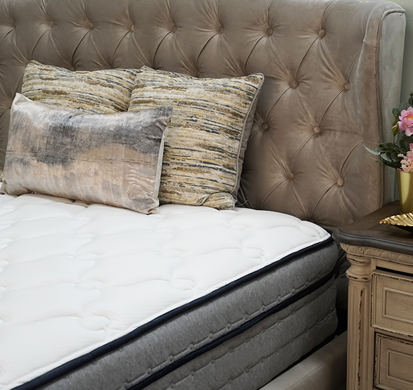 Corner of the Hanna Hybrid mattress on a brown bed