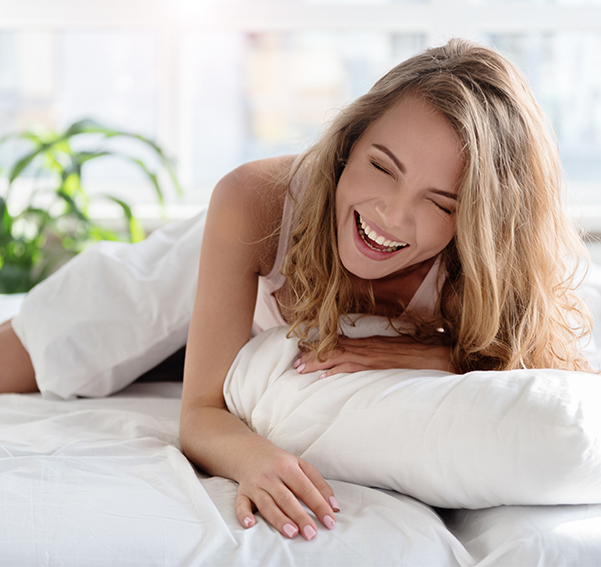 Young lady enjoying Sweet Zzz bamboo sheets in the white color