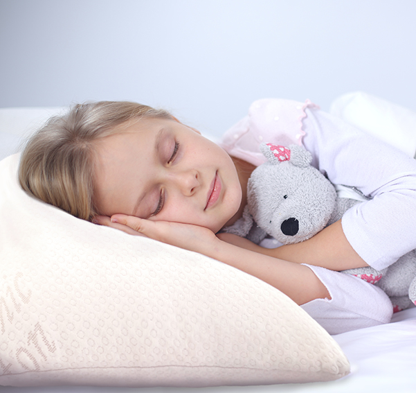 A little girl smiling while sleeping on the Sweet Zzz Latex Pillow