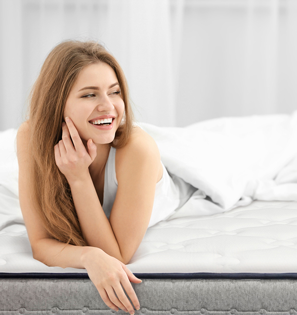 Young lady lying on the Hanna Hybrid mattress and smiling
