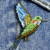 Embroidered & Beaded Tropical Hummingbird Pin, close up, on clothing