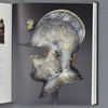 Interior of book Arms and Armor: Highlights from the Philadelphia Museum of Art with Helmet Pin