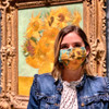 Van Gogh Sunflower Face Mask by Ana Thorne being worn by a woman in front of van Gogh painting