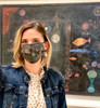 Klee Fish Magic Face Mask by Ana Thorne worn by a woman in front of Fish Magic painting